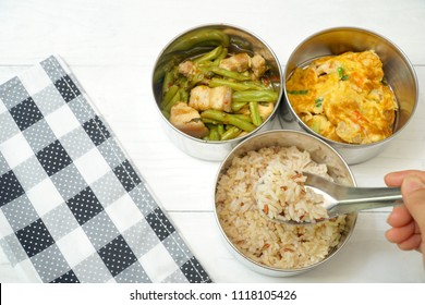 Focus of brown rice in spoon. Antique stainless steel food carrier (Tiffin food container) on wood background. Stir fried string bean and pork, Omelette with shrimp (Omelet). Simple style. Slow life