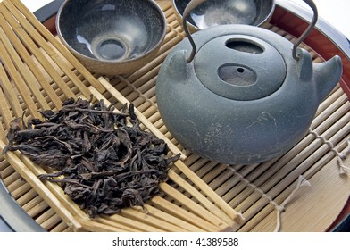 Focus at the dry oolong tea with a set of oriental teapot and cups.