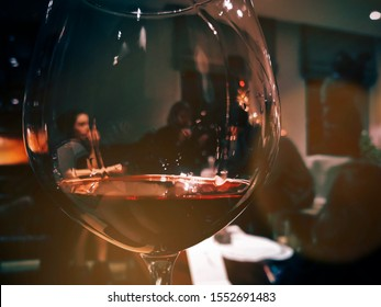 focus in foreground of a glass of red wine - background out of focus of a family in a warm indoor environment