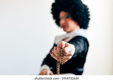 Focus in the foreground on hand holding a gold crucifix. defocused drag queen disguised as a nun in background. misogyny and homophobia in Catholic culture concept.