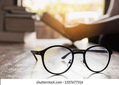 focus at glasses and background of woman sitting in a cafe, reading book.