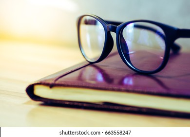 focus glasses,books stack on wooden desk