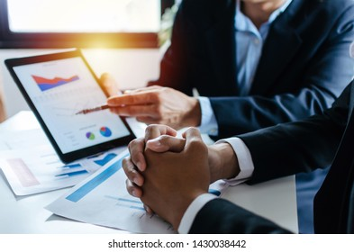 focus hand of partner business man investor talking about financial statistics chart information in mobile tablet together sitting in meeting room at office, finance, investment, technology concept
