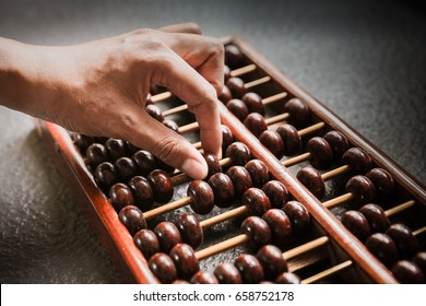 Focus Human Hand counting with wooden abacus
