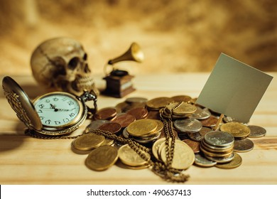 Focus in label Gray.Pile of money, Thai coins of one bath on wood element antique clock,skull,vintage gramophone background.Concept of financial planning and savings.Vintage tone.