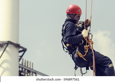 Focus male worker using rope access of inspection storage tank