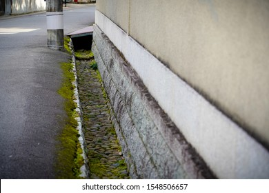 Focus natural stone Japanese waterspout on side road next the wall,Japanese gutter design construct by many rocks with green moss covering.