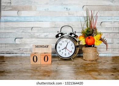 Focus object silver vintage clock and nature wood block with text and number ,on wood table and vintage wood background, start for monday working and due date remember background concept,