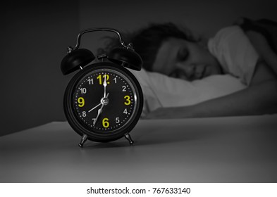 Focus on the alarm clock in front of sleeping woman at night in the bedroom