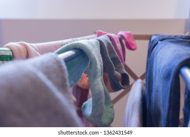 Focus on ankle socks drying on a laundry rack with other woman's clothes, including blue jeans. Mismatched socks and pair of matched socks in background.