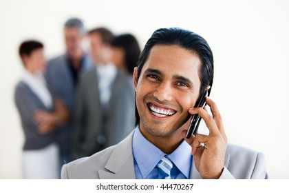 Focus on an assertive ethnic businessman on phone against a white background