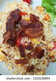 focus on Bacon. Thai fried rice with bacon on top. Mixed eastern and western food to serve world wide customers. This dish has rice , bacon, tomatoes, eggs, Simple and delicious food of the day.