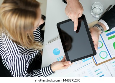Focus on biz woman looking at new modern gadget with great interest. Smart businessman pointing at something on notepad. Copy space on digital tablet. Blurred background