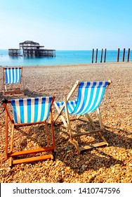 Focus on blue and white striped deckchairs on pebble beach in Brighton - burnt  pier in the distance with bright blue sky and multicoloured pebbles and blue ocean. Shadows from chairs showing on beach