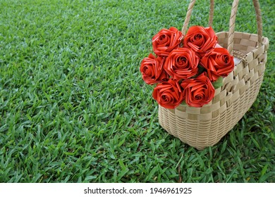 Focus on the bouquet of red roses in the basket weave on the lawn. Artificial roses from ribbons. - Shutterstock ID 1946961925