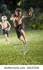 Focus on boy, 9 years, jumping through water spray from lawn sprinkler