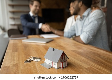 Focus on close up keys bunch and cottage house toy model on wooden table. Smiling young man broker realtor real estate agent shake hands of happy black couple clients homeowners on blurred background