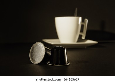 Focus on coffee capsules with in the back out of focus a cup of coffee