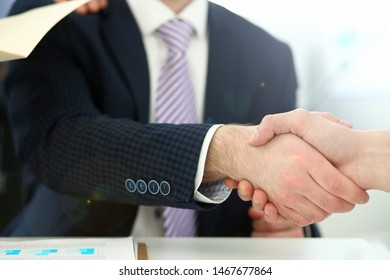 Focus on colleague performing friendly gesture and trying to politely greet colleague or worker friend. Smart man wearing classy clothes. Company meeting concept. Blurred background