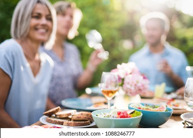 Focus on a colored salad in a bowl, Friends gather to share a meal around a table in the garden. Focus on the foreground