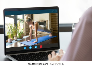 Focus on computer screen with fit young woman standing in plank position, enjoying practicing yoga on mat alone at home. Strong female fitness trainer giving online educational pilates workshop.