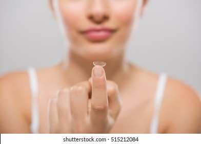 Focus on contact lens on finger of young woman. Young woman holding contact lens on finger in front of her face. Woman holding contact lens on grey background. Eyesight and eyecare concept.