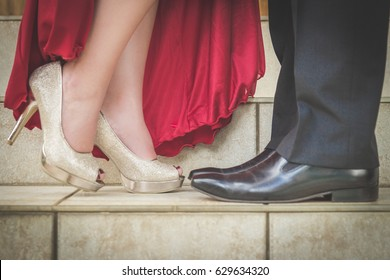 Focus on couples feet in dress shoes in formal wear facing each other with woman's leg lifted while kissing