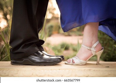 Focus on couples feet in dress shoes in formal wear facing each other with woman in blue dress and silver high heel shoes closeup