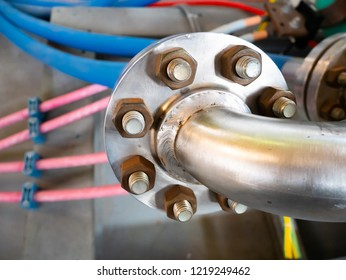 focus on coupling with heavy metal flange, high pressure, with screws and large bolts on an industrial elbow piping