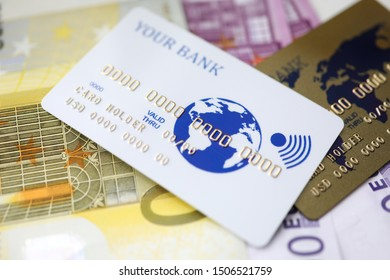 Focus on credit card with bank and card holder name. Bankcard lying on banknotes. World map painting on creditcard. Finance and business concept. Blurred background