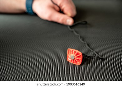 Focus on exercise equipment emergency stop laying on a treadmill belt with a Caucasian hand in the background