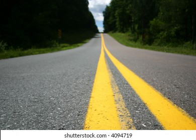 Focus on extreme foreground. Road with yellow stripe; trees and sky in distance over small rise in road.