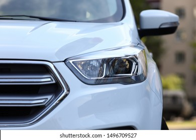 Focus on fashionable white business automobile. Bumper, silver radiator grille and headlamp of stylish vehicle. Buying new auto concept. Blurred background