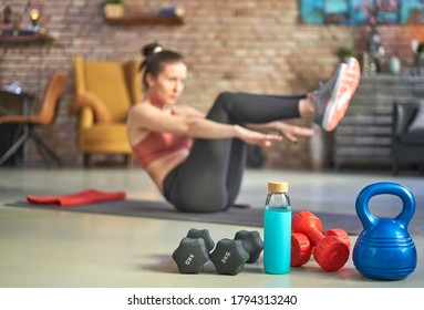 Focus on fitness equipments, barbell and kettlebell. Woman doing sit-ups in the background. Concepts about home workout, fitness, sport and health.