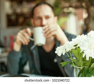 Focus on flowers. Defocus Background - young man drink coffee