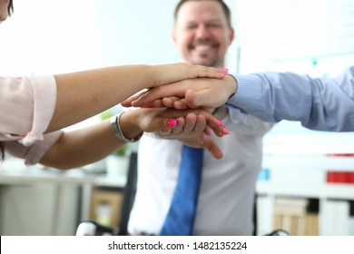Focus on folded hands of colleagues on each other. Managers underwriting good deal and celebrating closing bargain. Business meeting and teamwork concept