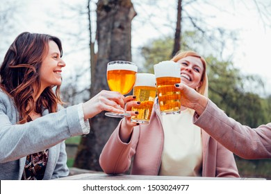 focus on the foreground of female hands holding beer mugs in an outdoor terrace in autumn. Toasting and celebrating and friendship concept