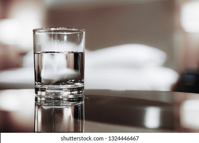 Focus on glass of water. Elegant and comfortable home & hotel bedroom interior with warm lights room as background.