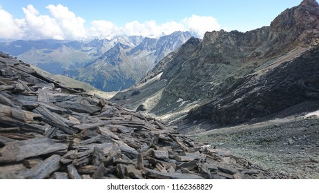 Focus on gneiss and schist long pebbles on Ignes Pass slopes with a blurred view of a distant Alpine panorama over Herens Valley in Swiss Alps on a cloudy Summer day