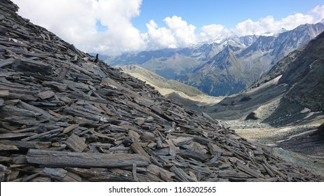 Focus on gneiss and schist long pebbles on slopes of Ignes Pass with a blurred view on a distant Alpine panorama over Herens Valley in Swiss Alps on a cloudy Summer day