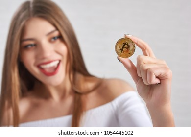 Focus on golden bitcoin as main digital currency and cryptocurrency hold by smiling beautiful female model. Horizontal shot, blurred background. Concept of web virtual money, mining.