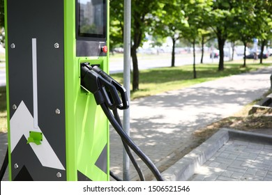 Focus on green power supply for electric automobile. Modern charge gun and pile on road for clean energy future of transportation. Environmental protection and newest transport technology concept