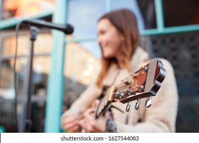 Focus On Guitar As Female Musician Busks And Sings Outdoors In Street