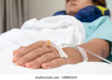 Focus on the hand of a patient near big window in hospital ward