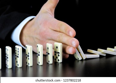 Focus on the hand of a young man in business clothes that prevents a chain reaction in a row of dominos by intervening - A leadership decision to prevent a chain reaction