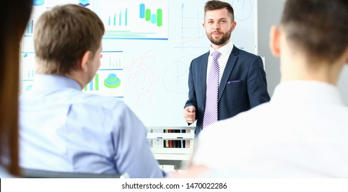 Focus on handsome smiling man. Chief executive officer conducting masterclass for colleagues. Staffs sitting in conference room. Company meeting concept