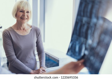 Focus on happy mature lady seeing surgeon in clinic. While doctor is holding X-ray film she is waiting for diagnosis. Copy space in right side