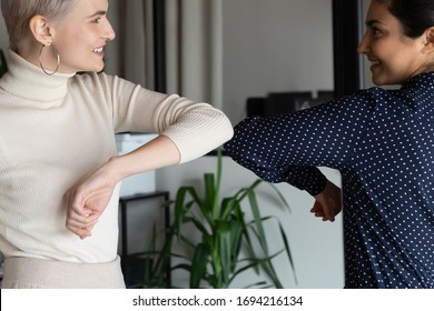 Focus on happy young female mixed race friendly colleagues bumping elbows, avoid handshaking hugs while greeting each other in office, preventing coronavirus infection spread, social distance concept.