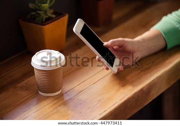 Focus on hipster woman using smartphone with drink at coffee shop