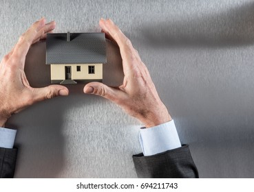 focus on a house symbol for concept of security, property development, real estate or housing project with businessman hands, copy space